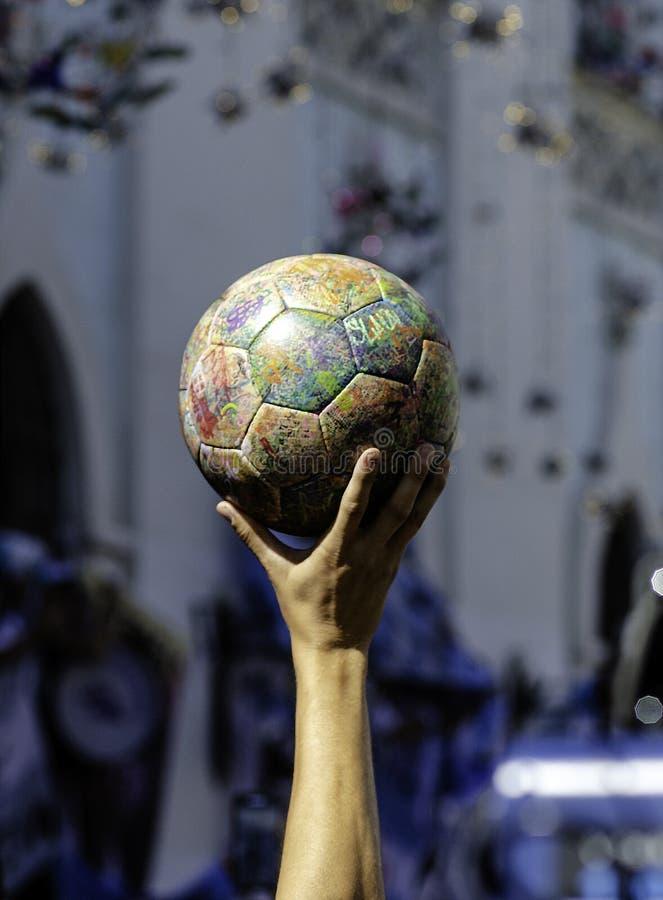 橄榄球在手中,看起来象世界杯 免版税图库摄影