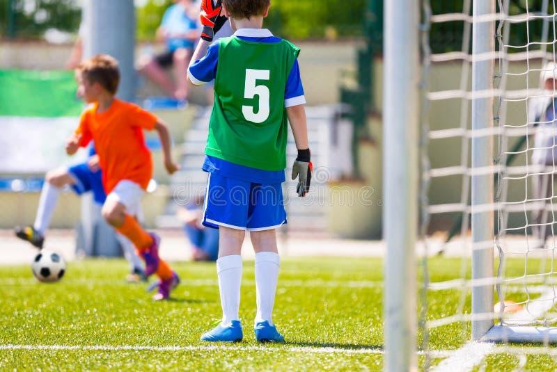 橄榄球孩子的训练比赛 作为站立在目标的橄榄球守门员的年轻男孩 追捕球的足球运动员 免版税库存照片