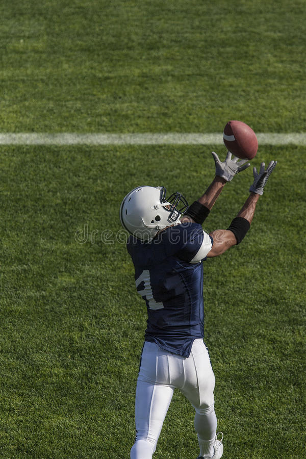 橄榄球捉住触地传球的运动员行动照片 免版税库存图片