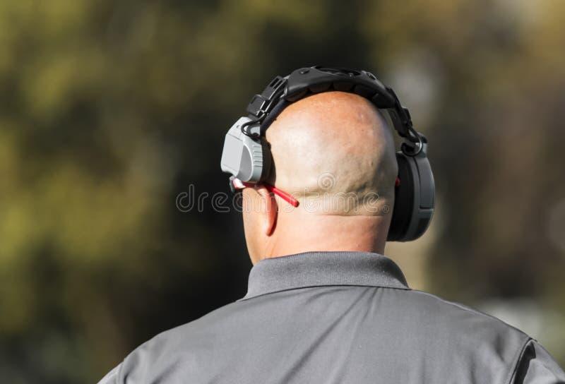 橄榄球教练从后面朝向,虽然他看得在前场 免版税库存照片