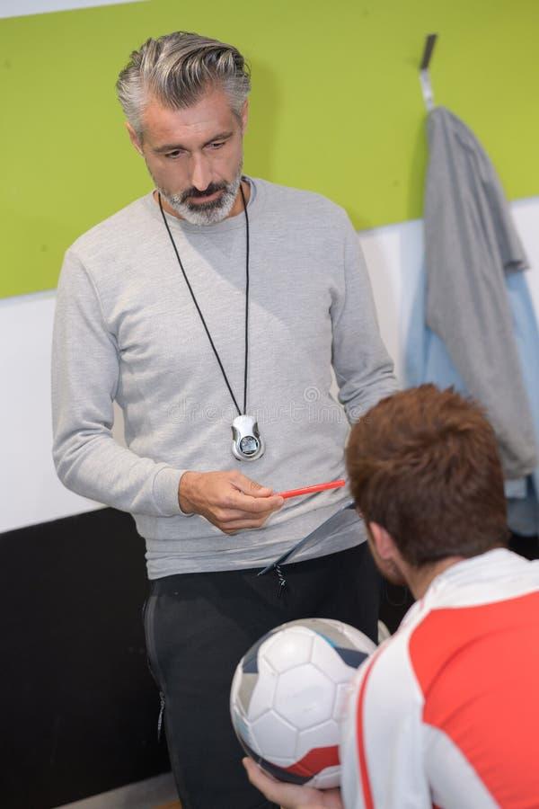 橄榄球教练谈话与球员在更衣室 免版税图库摄影