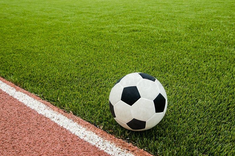 橄榄球是在人为草足球场的近的线 免版税库存照片
