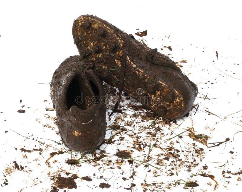 橄榄球泥泞的鞋子 库存照片
