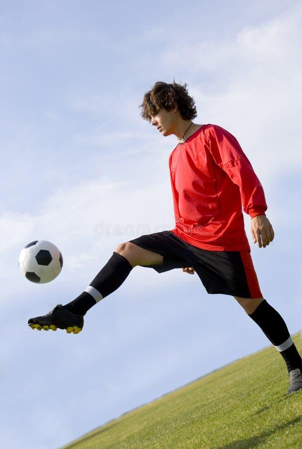 橄榄球玩杂耍的球员红色足球 库存照片
