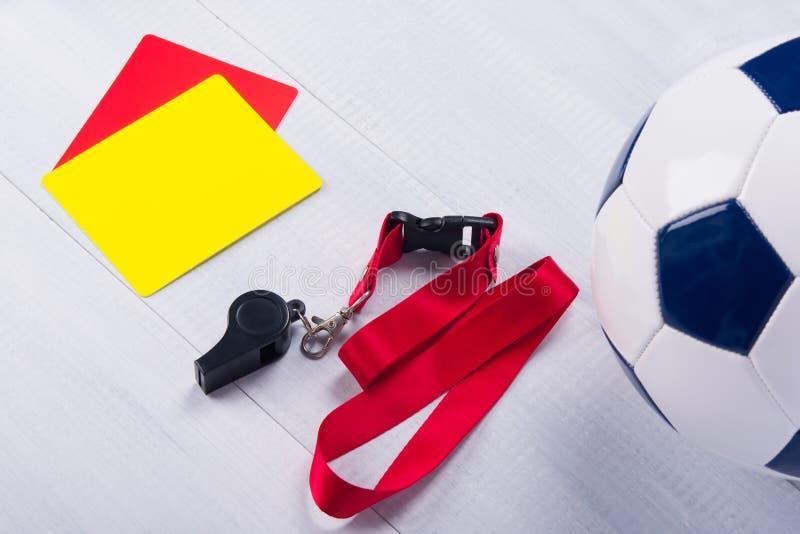 橄榄球球、两张惩罚卡片和一声口哨裁判员的,灰色背景的 免版税库存图片