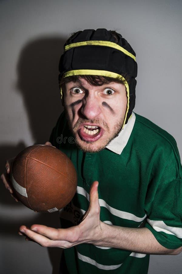 橄榄球球员藏品球在手中和做面孔 免版税库存图片