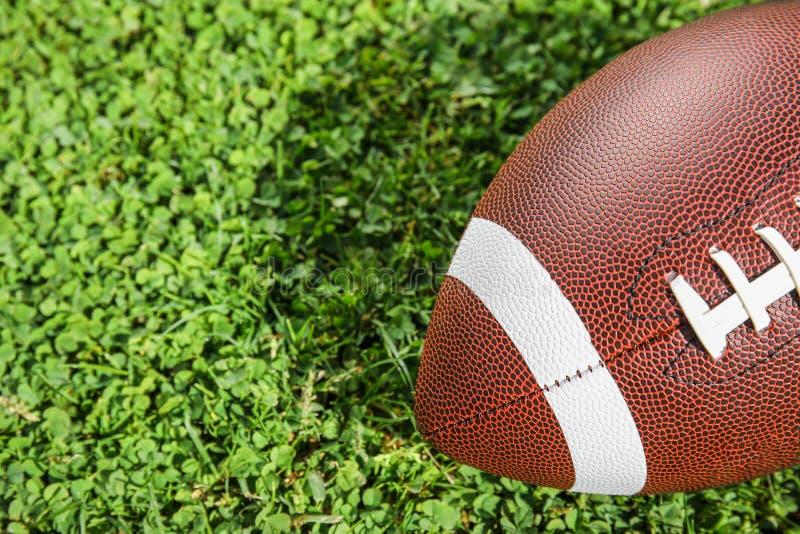 橄榄球的球在新鲜的绿色领域草,特写镜头 免版税图库摄影