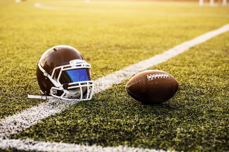 橄榄球盔甲和球在绿草样式橄榄球的炫耀,橄榄球场,足球场,团体性运动 免版税库存照片
