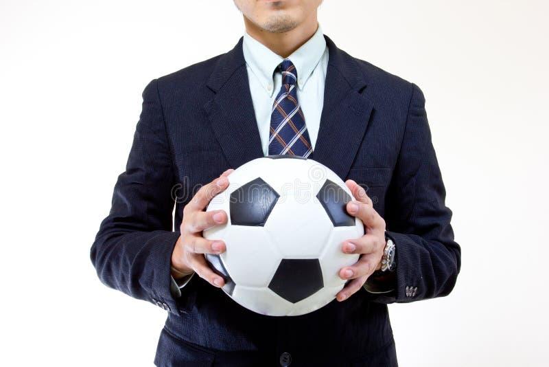 橄榄球经理暂挂球用他的现有量 库存照片