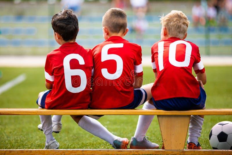 橄榄球足球儿童队 孩子替代球员坐长凳 免版税库存图片
