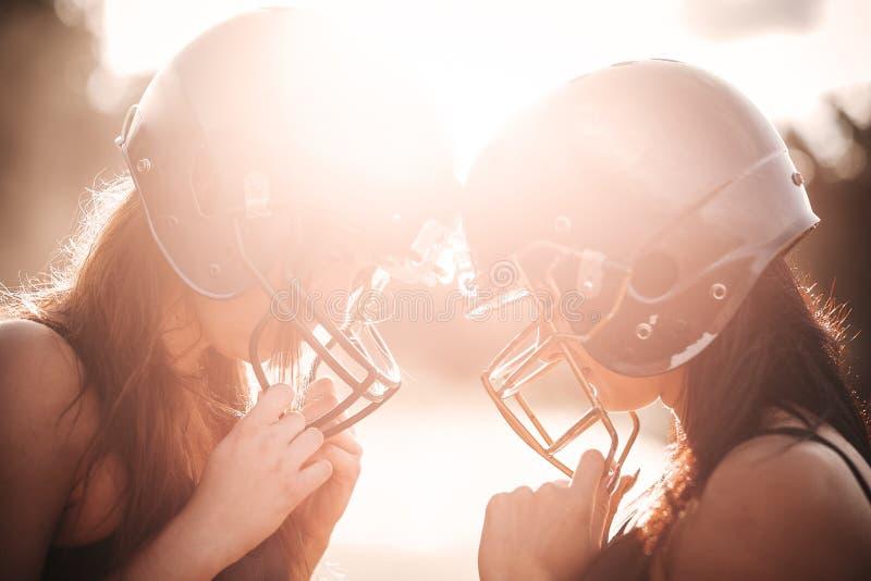 橄榄球足球选手制服的性感的年轻嬉戏女孩行动的对体育场 美式足球妇女球员逗留 免版税图库摄影