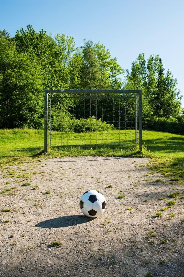 橄榄球,在惩罚斑点,青年时期的足球场的球 免版税库存照片