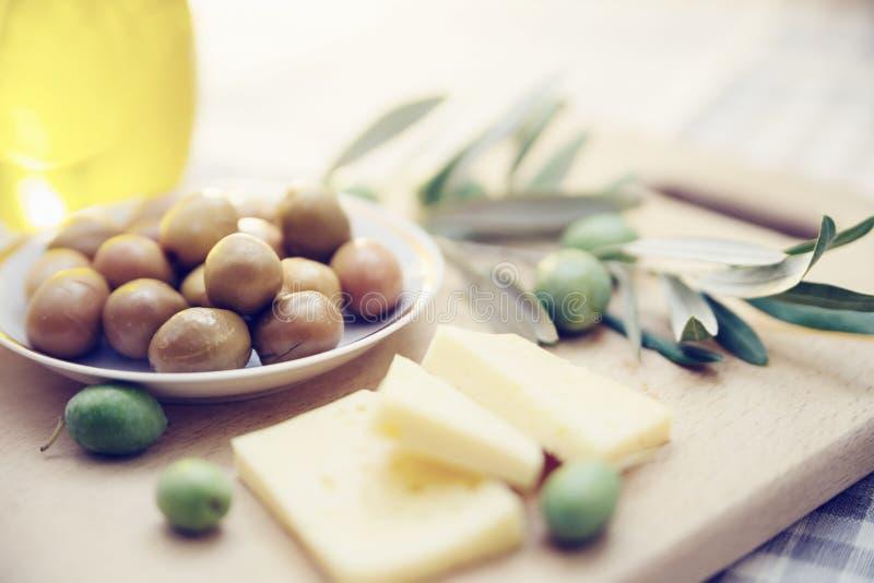 绿橄榄用乳酪和橄榄树枝在一个木板 库存图片
