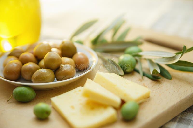 绿橄榄用乳酪和橄榄树枝在一个木板 免版税库存图片