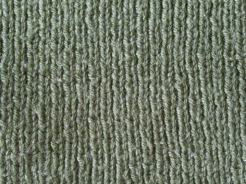 橄榄绿羊毛手工编织的纹理摘要背景 库存照片