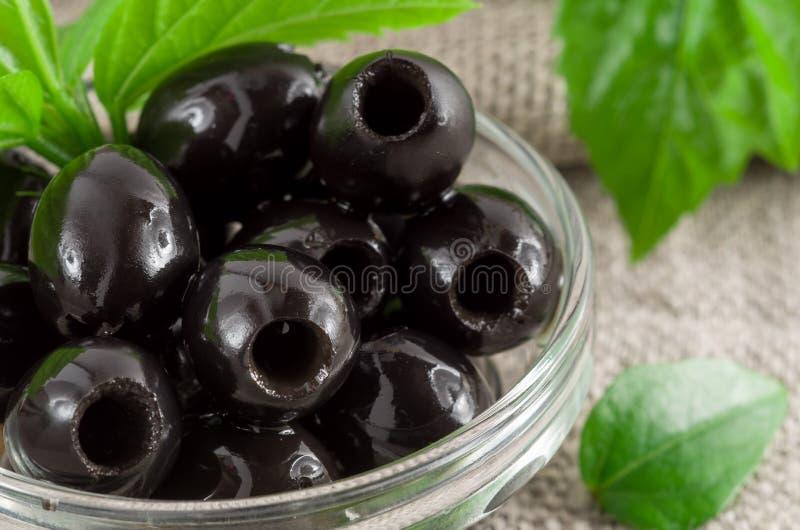 黑橄榄,挖坑用卤汁泡在一个玻璃碗 图库摄影