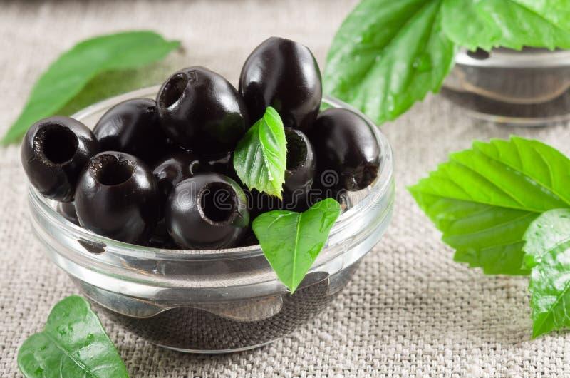 黑橄榄,挖坑用卤汁泡在一个玻璃碗 免版税库存图片