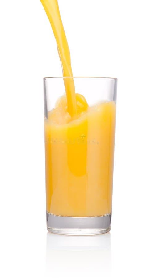 橙汁涌入在白色背景隔绝的玻璃 免版税库存图片
