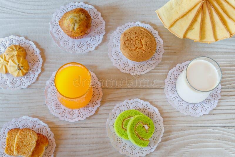 橙汁过去、牛奶、杯形蛋糕、蛋糕卷、蒜味面包、黄油面包、香蕉杯形蛋糕和曲奇饼 图库摄影