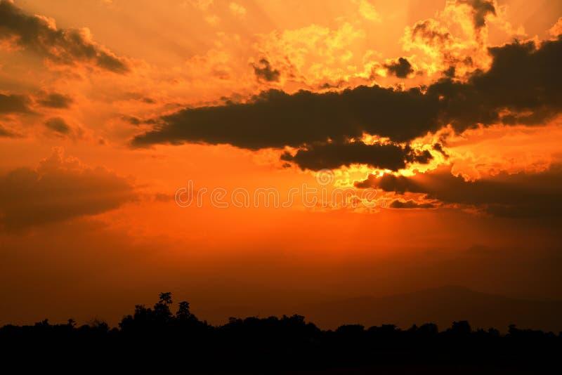 橙色光和黑暗的云彩在天空在山 免版税库存照片