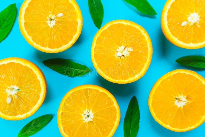橙色切片和薄荷叶的五颜六色的图片在明亮的蓝色背景 r 库存图片