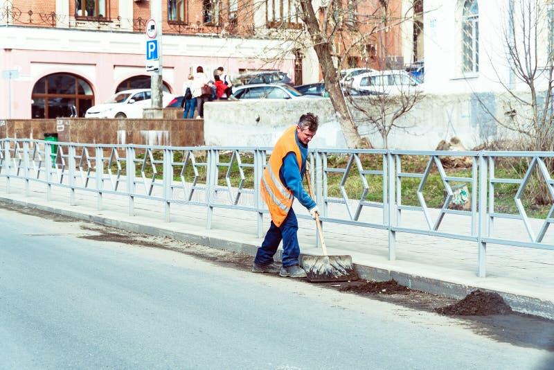 橙色制服的管理员清洗垃圾与在城市街道上的一把铁锹 免版税库存照片