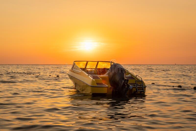 橙色和黄色日落接近的美好的海视图与一艘被停泊的汽艇的反对天际 库存图片