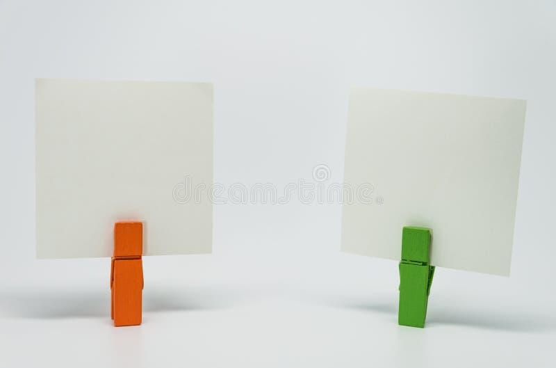 橙色和绿色木夹子夹紧的备忘录纸张有白色背景和选择聚焦 免版税库存照片