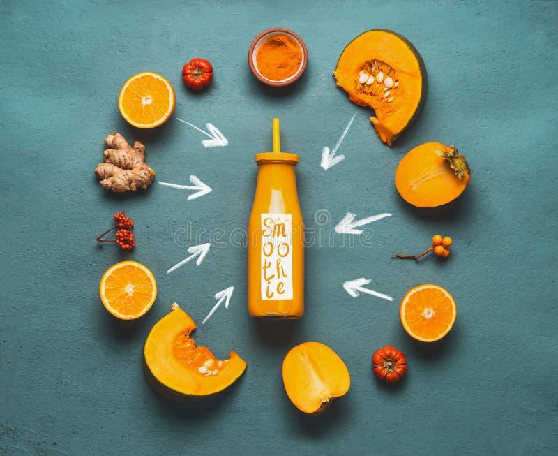 橙色圆滑的人成份:南瓜、柿子,橙色果子、姜和姜黄粉末在瓶附近 免版税库存图片