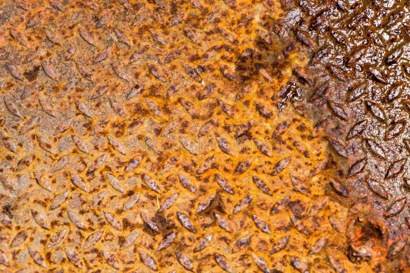 橙色土气金属片与一旁边弄湿了 免版税图库摄影