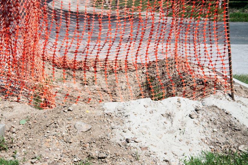 橙色塑料安全网或障碍在保护挖掘的建造场所关闭的街道上  免版税库存图片
