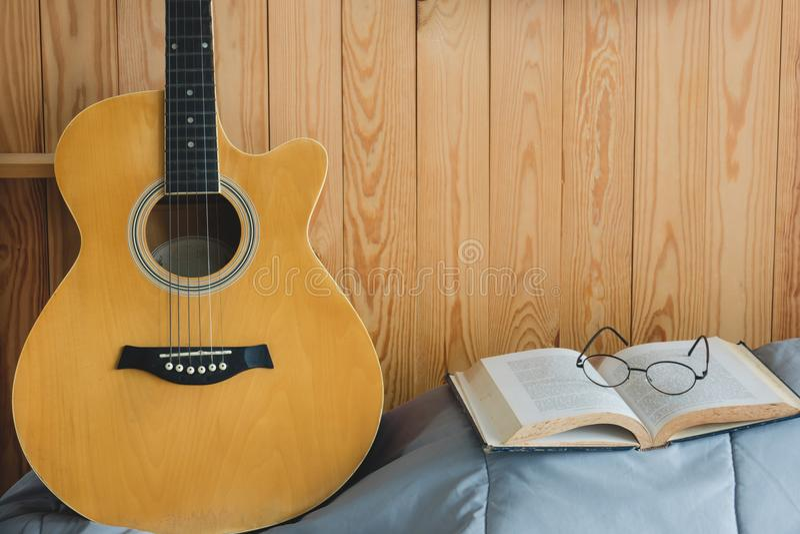 橙色声学吉他和开放书与镜片 免版税图库摄影