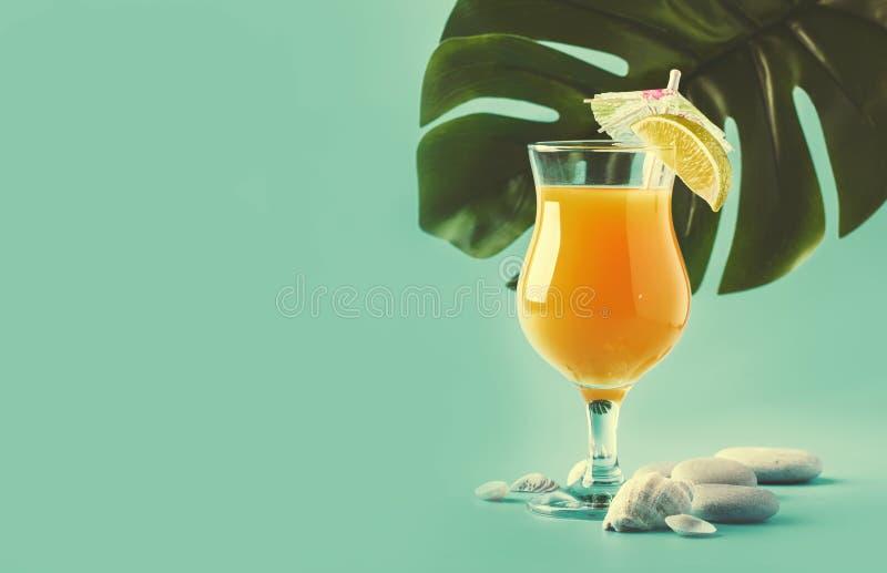 橙色夏天酒精鸡尾酒用芒果汁、兰姆酒、利口酒、石灰和冰,蓝色背景,拷贝空间 库存图片
