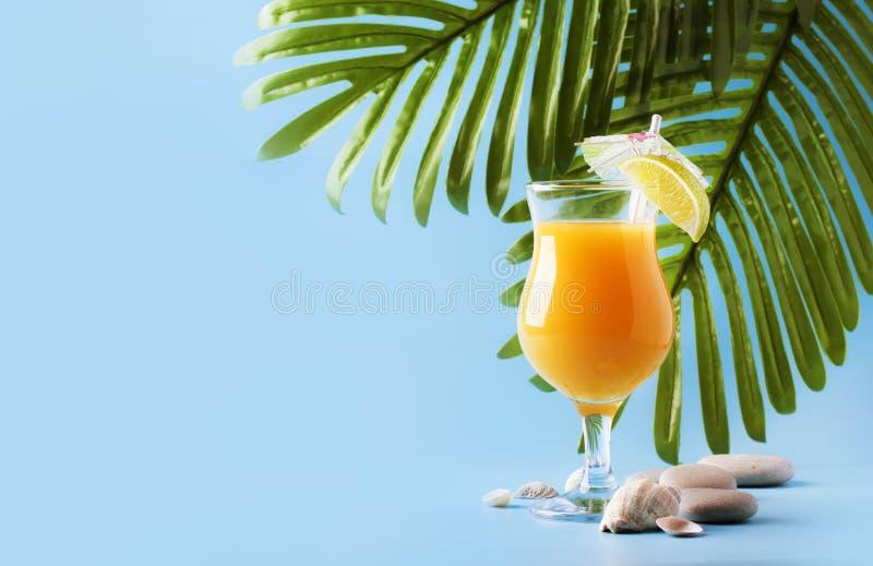 橙色夏天酒精鸡尾酒用芒果汁、兰姆酒、利口酒、石灰和冰,蓝色背景,拷贝空间 免版税库存照片
