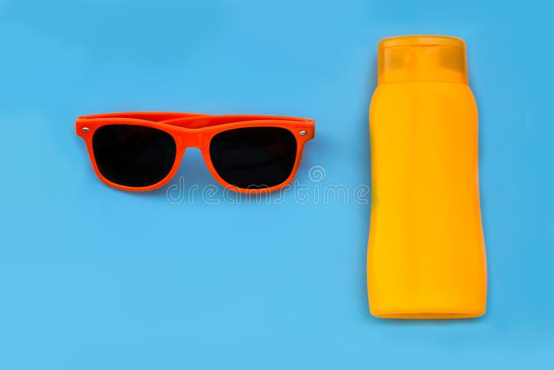 橙色太阳镜和橙色瓶suncream或太阳化妆水在强烈的蓝色背景中隔绝了平的位置 免版税库存图片