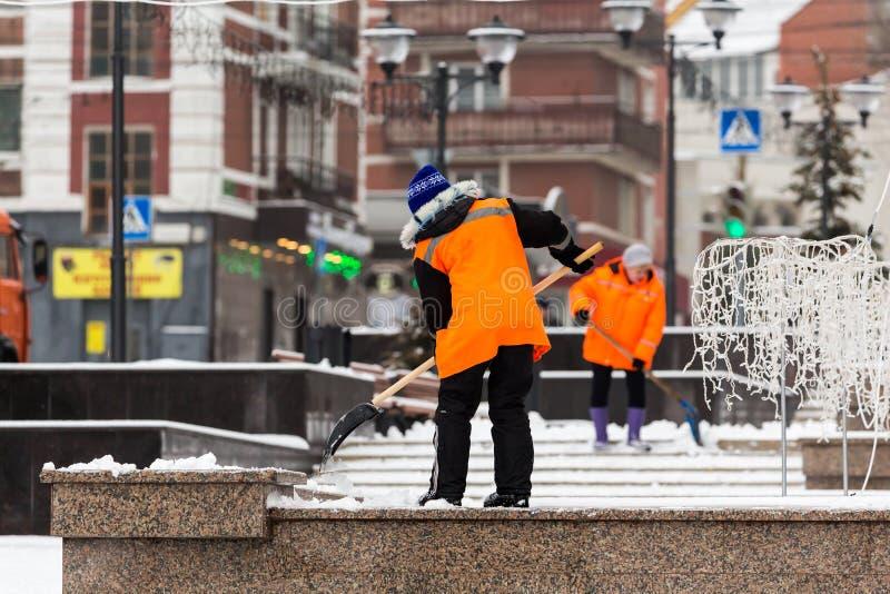 橙色夹克的人民管理员从雪清洗了城市与铁锹 在以后的冬天城市降雪 免版税库存照片