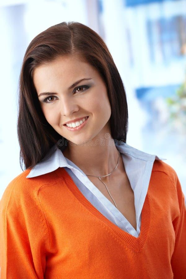 橙色套头衫微笑的美丽的妇女 免版税库存图片