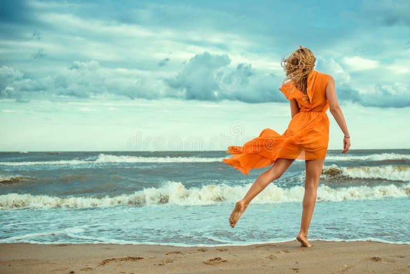橙色套衫连超短裙的美丽的妇女与赤足跳舞在湿沙子的飞行火车在猛冲的海 库存图片