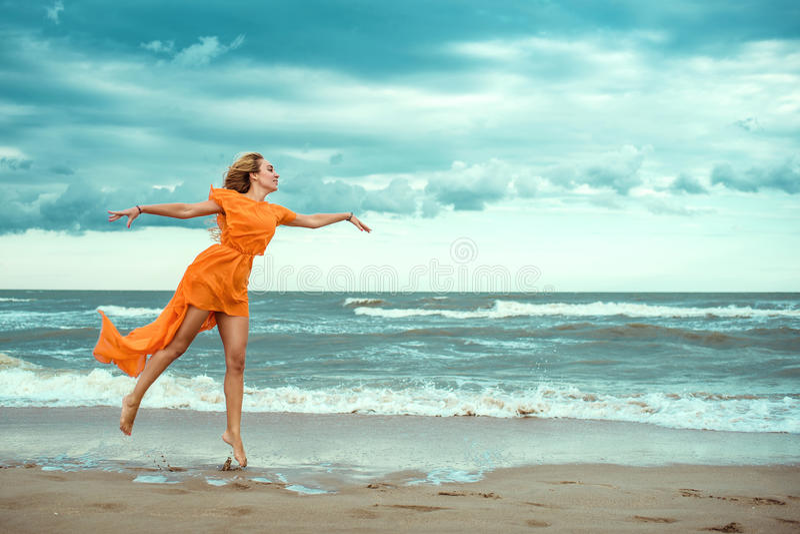橙色套衫连超短裙的美丽的白肤金发的妇女与赤足跳舞在湿沙子的飞行火车在猛冲的海 免版税库存照片