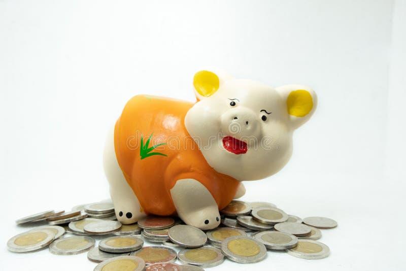 橙色存钱罐攒钱和硬币堆 免版税库存照片