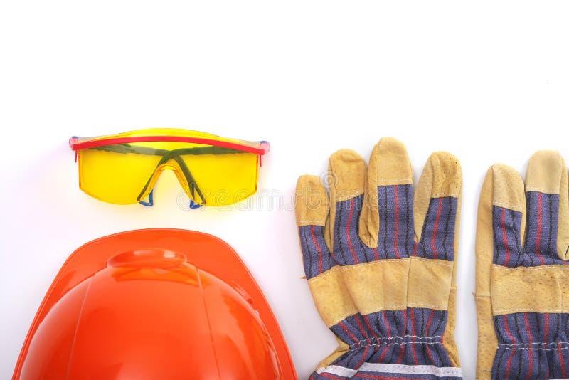 橙色安全帽、皮革工作手套和安全玻璃在白色背景 复制空间 免版税库存照片