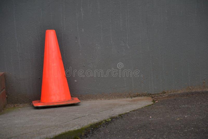 橙色安全锥体对灰色大厦墙壁在波特兰,俄勒冈 库存照片