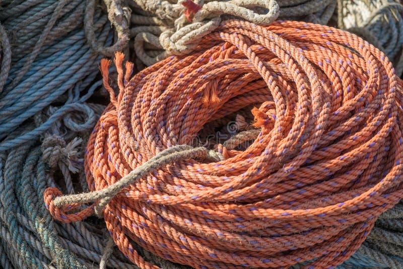 橙色尼龙绳索在一个运作的船坞盘绕了和准备好待用 库存照片