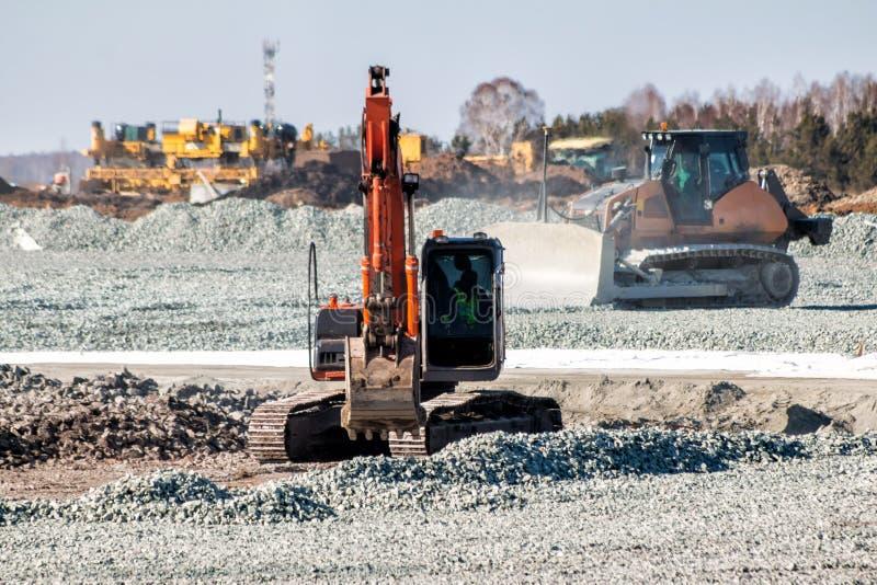 橙色挖掘机和黄色推土机在修路清疏瓦砾 库存图片