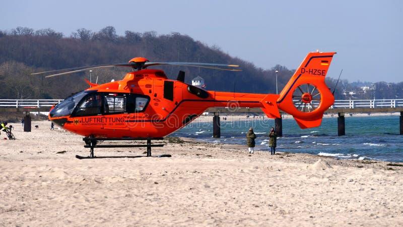橙色救援直升机降落在沙滩上 图库摄影