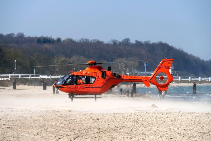 橙色救援直升机降落在沙滩上 库存照片