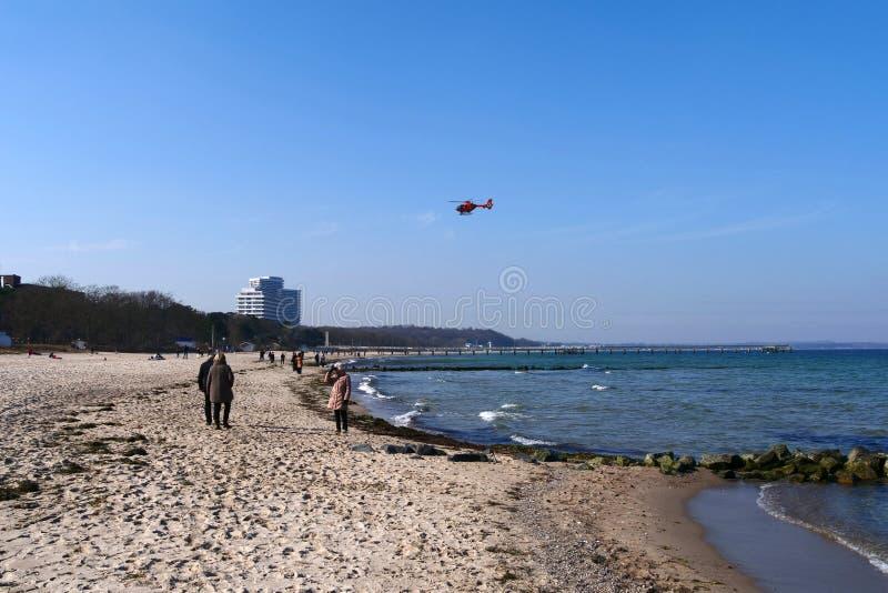 橙色救援直升机降落在沙滩上 库存图片