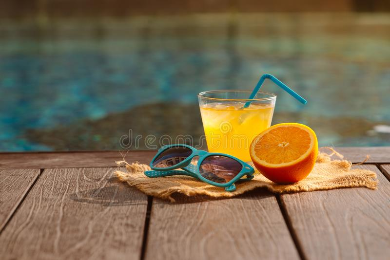 橙色新汁液圆滑的人饮料,太阳镜临近游泳池 库存图片