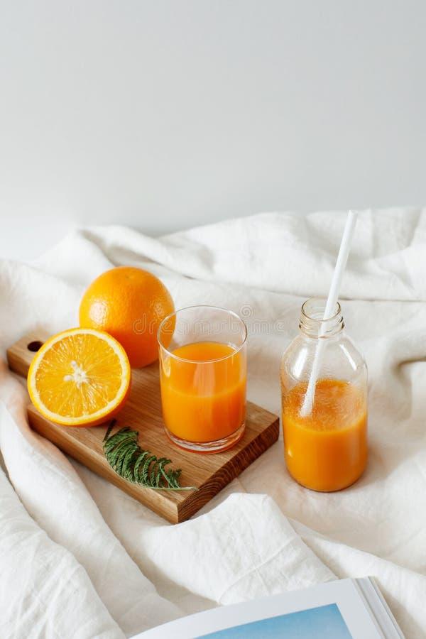 橙色新鲜早餐在玻璃和在有str的一个瓶 免版税库存照片