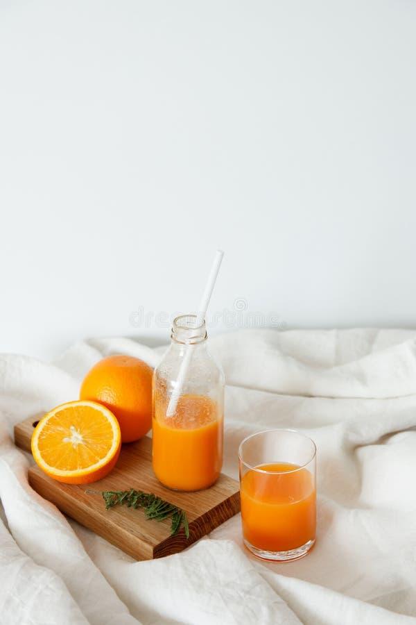 橙色新鲜早餐在玻璃和在有str的一个瓶 库存图片